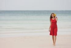 Attractive woman walking on beach Stock Photo