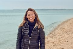 Attractive woman walking on a beach on a cloudy day. Wearing a backpack and jacket pausing at the edge of the sea to smile at the camera stock photo