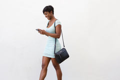 Attractive woman walking and looking at cell phone Stock Photo