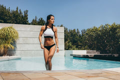 Attractive woman walking out of swimming pool Royalty Free Stock Photo