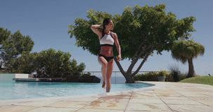 Attractive woman walking out of swimming pool stock video