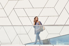 Attractive woman walking outdoors and talking on cell phone Royalty Free Stock Photos