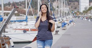 Attractive woman walking past a marina stock video footage