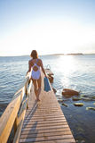 Attractive woman walking on pier. Attractive woman in white bathing suit walking on wooden pier in nordic country during summer Royalty Free Stock Photos