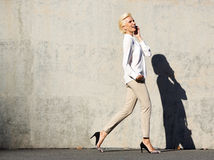 Attractive woman walking and talking on mobile phone Royalty Free Stock Photo