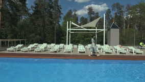 Attractive woman walks over the pool in the leisure club stock video footage