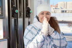 Attractive woman warming hands in petrol station Stock Photos