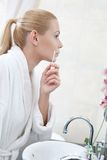 Attractive woman washes face with lotion Stock Photos