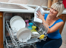 Attractive woman washing dishes Stock Photos