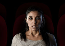 Attractive woman watching thriller or suspense drama movie alone at cinema hall theater Royalty Free Stock Images