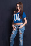 Attractive woman wear blue crop top and ripped blue jean pants. Good looking young woman with long straight hair, wear belly shirt and ripped blue jean pants Stock Photography