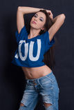 Attractive woman wear blue crop top and ripped blue jean pants Royalty Free Stock Photo