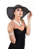 Attractive woman wearing black dress, hat and pearls Stock Photography