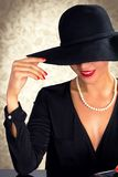 Attractive woman wearing black dress, hat and pearls. Sitting on black table Royalty Free Stock Photo