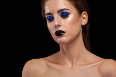 Attractive woman wearing blue make up with black lips. In studio photo. Beauty and fashion. Cosmetic and creative artistic make up Royalty Free Stock Photography
