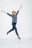 Attractive woman wearing eyeglasses jumping Royalty Free Stock Image