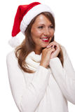 Attractive woman wearing a festive red Santa hat Royalty Free Stock Photos