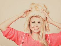 Attractive woman wearing furry winter hat. Outfit for cold days ideas, fashion and clothing concept. Attractive smiling blonde woman wearing furry winter hat Royalty Free Stock Image
