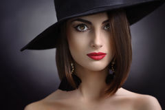 Attractive woman wearing a hat posing on black background Stock Image