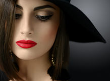 Attractive woman wearing a hat posing on black background. Cropped close up of a sexy red lipped young dark haired woman in a hat posing looking away sensually Royalty Free Stock Photos