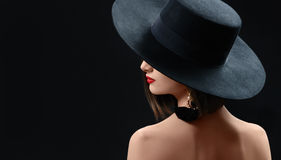 Attractive woman wearing a hat posing on black background. Rearview shot of a mysterious sexy red lipped brunette woman in a hat posing gracefully on black Stock Photo
