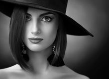 Attractive woman wearing a hat posing on black background. Black and white close up of a beautiful elegant woman wearing a wide hat posing in studio copyspace Stock Photo