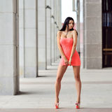 Attractive woman wearing red dress and posing in the city Royalty Free Stock Images