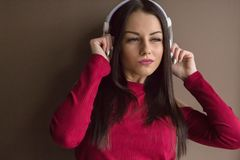 Attractive woman wearing red sweater in headphones Stock Photo