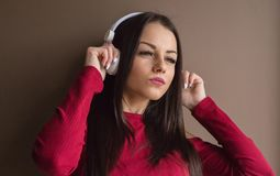 Attractive woman wearing red sweater in headphones Stock Images