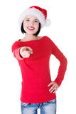 Attractive woman wearing santa hat is pointing. Royalty Free Stock Photo