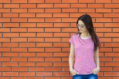Attractive woman wearing striped t-shirt and fashionable sunglasses posing against red brick wall, swag street style. Empty backgr. Ound Royalty Free Stock Photography