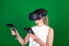 Woman wearing virtual reality headset with handheld  controllers. Attractive woman wearing virtual reality headset with two handheld trackpads or controllers in Stock Photography