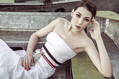 Attractive woman wearing white summer dress sitting in wooden bo. At Royalty Free Stock Photography