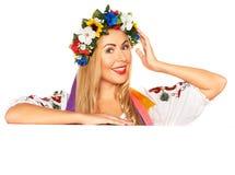 Attractive woman wears Ukrainian dress behind white board Royalty Free Stock Photos