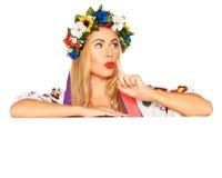 Attractive woman wears Ukrainian dress behind white board Royalty Free Stock Photo