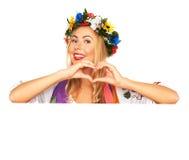 Attractive woman wears Ukrainian dress behind white board Stock Photo