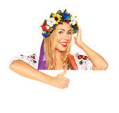 Attractive woman wears Ukrainian dress behind white board Stock Photo