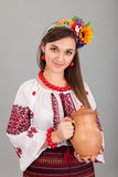 Attractive woman wears Ukrainian is holding a jug national dress Stock Photography