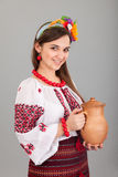 Attractive woman wears Ukrainian is holding a jug national dress Royalty Free Stock Photos