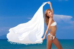 Attractive woman in white bikini holding scarf Royalty Free Stock Photo