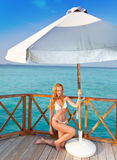 The attractive woman in white bikini sunbathes on a wooden terrace against the tropical ocean Stock Images