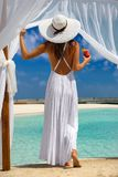 Woman enjoys the view to a tropical beach with a drink in her hand. Attractive woman in a white dress enjoys the view to a tropical beach with a drink in her royalty free stock photography