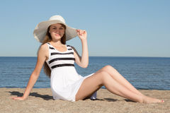 Attractive woman in white dress and hat sitting on the beach Stock Image