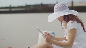 Attractive woman in a white dress and sun hat using a tablet on the beach, in slow motion stock video