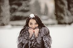 Attractive woman in white and gray fur coat