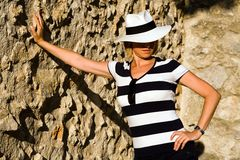 Attractive woman in white hat standing by wall Stock Image