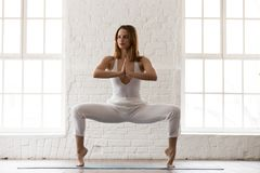 Attractive woman standing in Goddess pose, Sumo Squat, yoga exercise. Attractive woman in white sportswear, pants and top standing in Goddess pose, Sumo Squat royalty free stock photos
