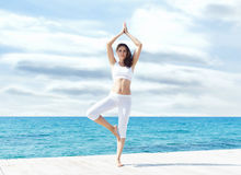 Attractive woman in white sporty clothes doing yoga on a wooden. Pier. Yoga, sport, leisure, recreation and freedom concept Royalty Free Stock Image