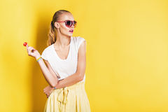 Attractive woman in white top with lollipop in hand Stock Photography