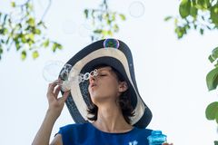 Attractive woman in a wide brimmed sunhat blowing bubbles. Under tree on a hot sunny summer day Stock Photography